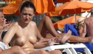 Pierced nipple chick spraying on sunscreen