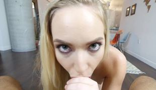A blond with a slim body is placing her mouth around a large dick to suck
