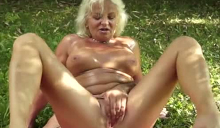 Blonde and busty cougar rides a big dick in the forest