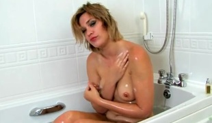 Milf soaps up her bushy snatch in the bathtub